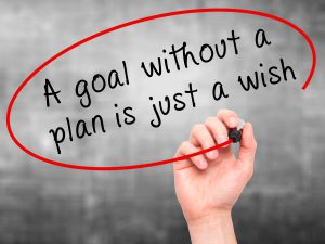 "Man Hand writing ""A goal without a plan is just a wish"" black ma"